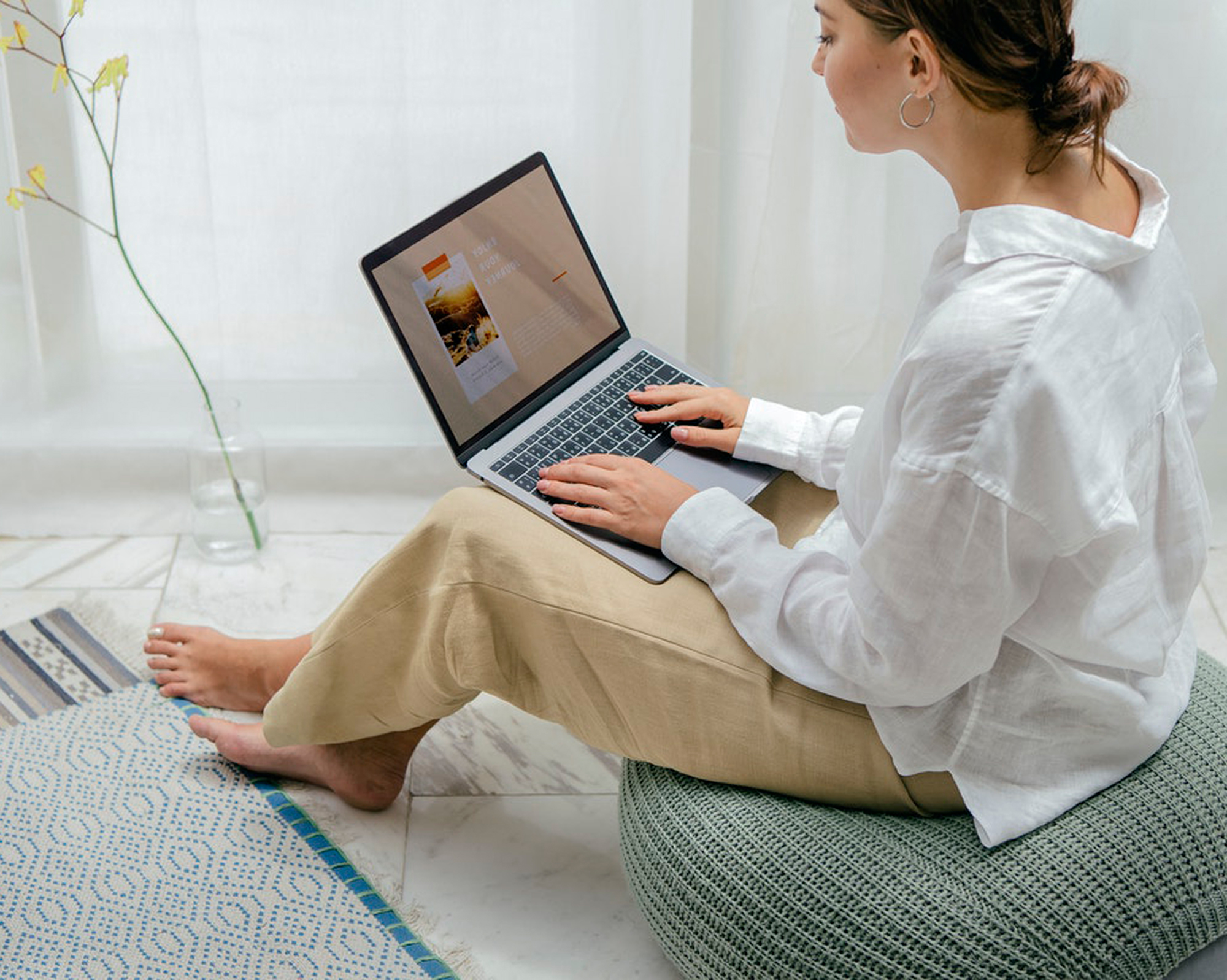Lady looking at laptop while sitting on a bean bag