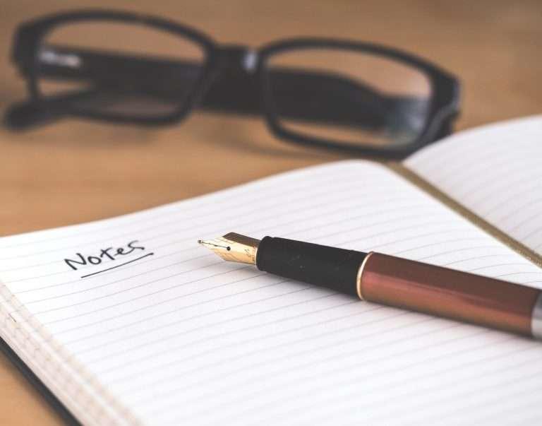 Notepad, pen, glasses on desk
