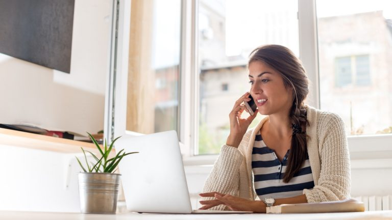 Woman talking on phone and looking at her laptop monitor
