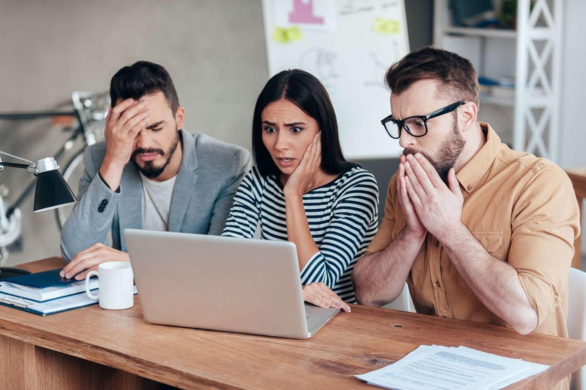 Team members looking shocked at computer monitor